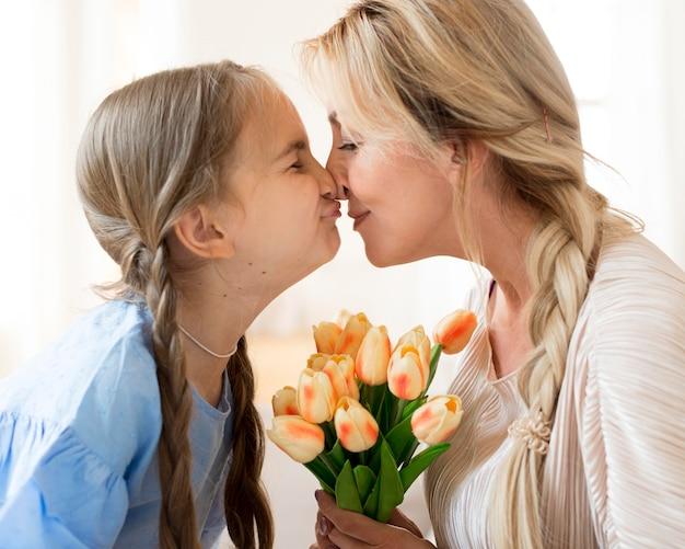 Dochter die moederboeket van bloemen geeft