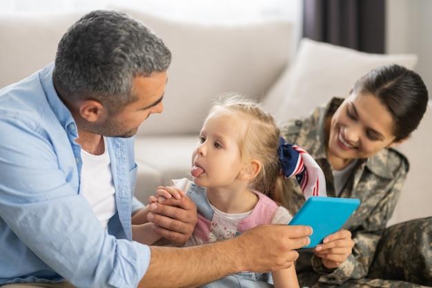 Dochter die tong toont. grappige blondharige dochter die haar tong aan papa laat zien terwijl ze plezier heeft met het gezin