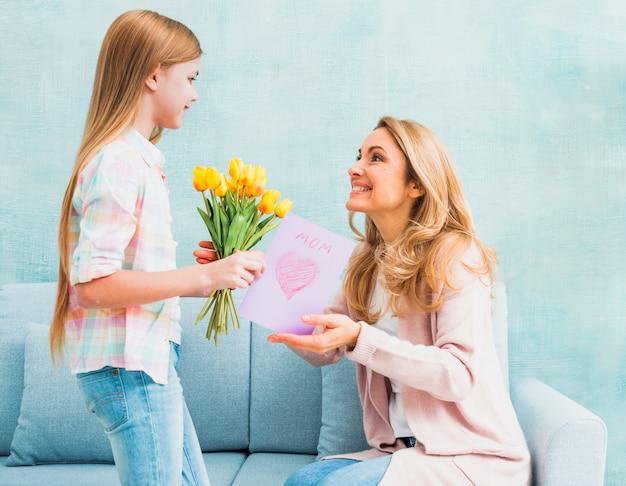 Dochter die tulpen en prentbriefkaar voor moeder voorstelt