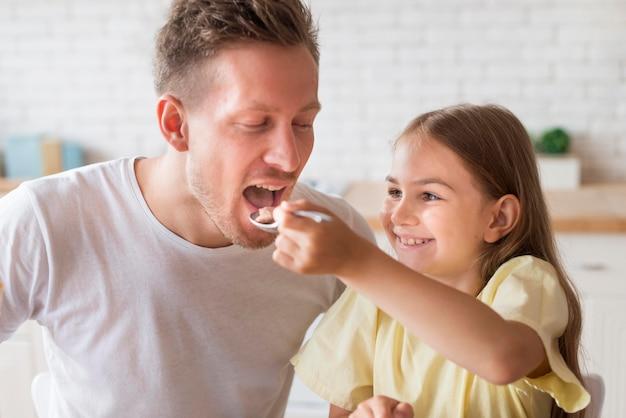 Dochter die voedsel geeft aan vader
