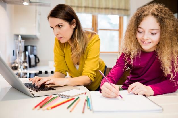 Dochter doet haar huiswerk en moeder werken op de laptop in kitc