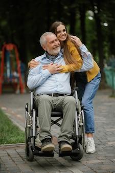 Dochter en gehandicapte vader in rolstoel, gelukkige familie wandelen in het park. verlamde mensen en handicap, handicap overwinnen. gehandicapte mannelijke persoon en jonge vrouwelijke voogd in openbare ruimte