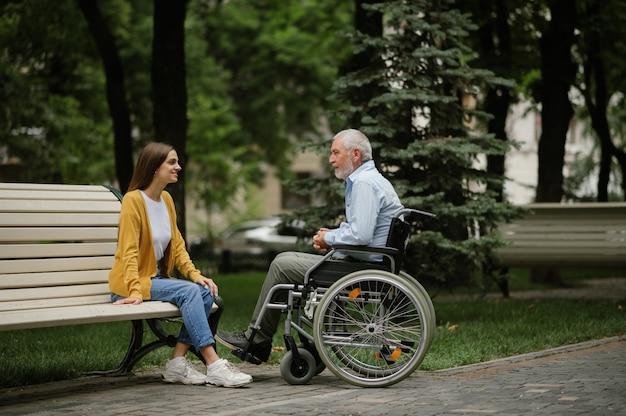 Dochter en gehandicapte vader in rolstoel rustend op een bankje. verlamde mensen en handicap, handicap overwinnen. gehandicapte mannelijke persoon en jonge vrouwelijke voogd vrije tijd in openbare ruimte