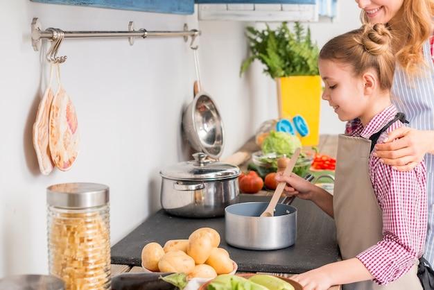 Dochter en haar moeder die soep in de keuken koken