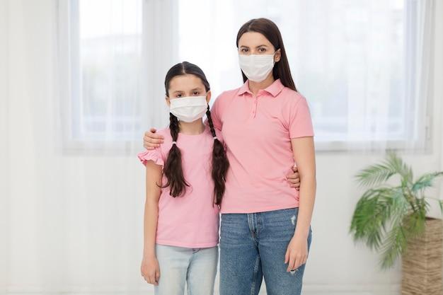 Dochter en meisje dat maskers draagt