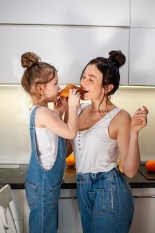 Dochter en moeder delen een smakelijke croissant samen