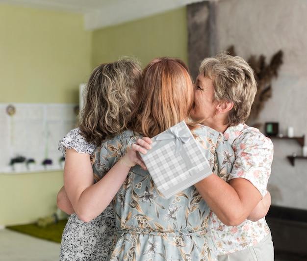 Dochter en moeder die hogere vrouw met de doos van de holdingsgift kussen