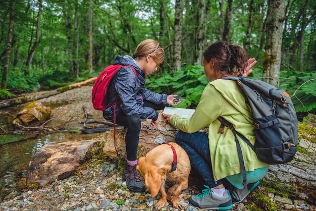 Dochter en moeder die in bos wandelen en kompas gebruiken
