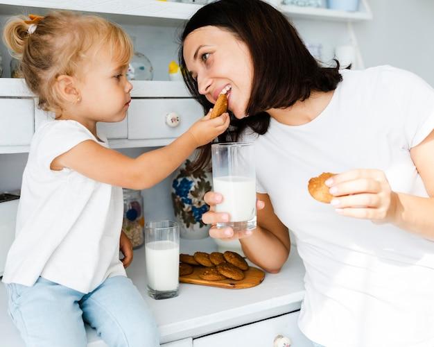 Dochter en moeder die koekjes eten