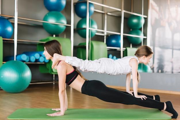Dochter en moeder die samen bij gymnastiek uitoefenen