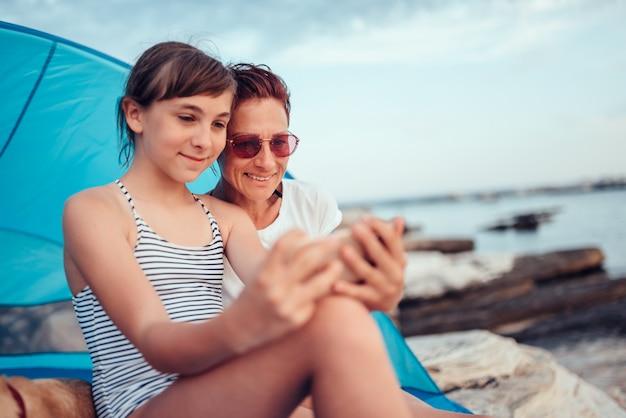 Dochter en moeder die selfie met slimme telefoon op het strand nemen