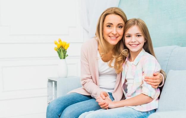 Dochter en moeder glimlachend en knuffelen