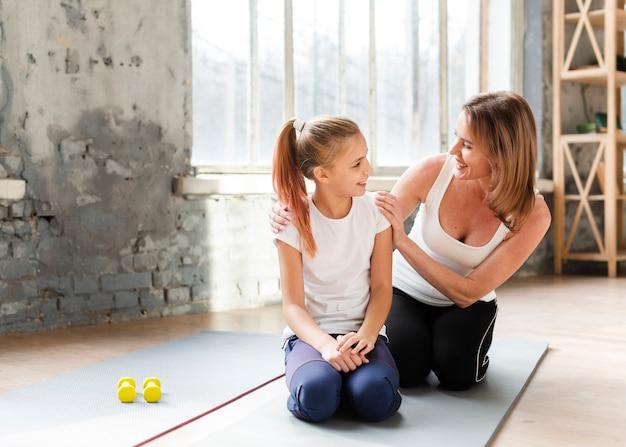 Dochter en moeder kijken elkaar op yogamatten