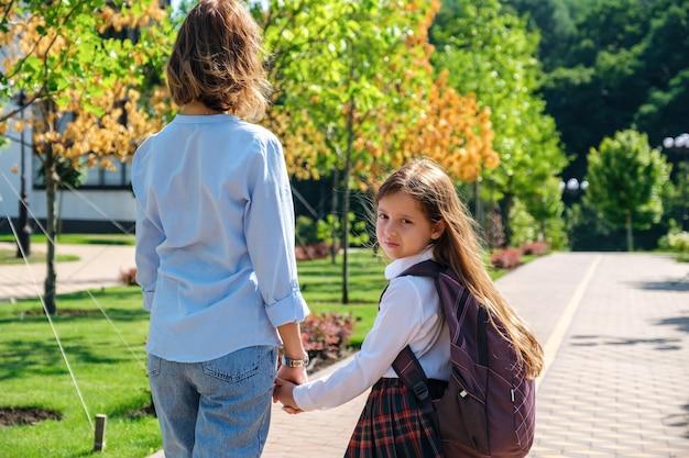 Dochter en moeder lopen samen naar school verderop in de straat