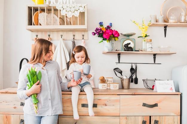 Dochter en moeder met bloemen die thee drinken