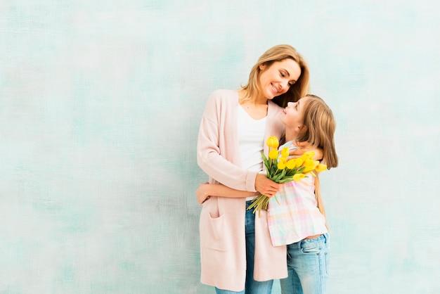 Dochter en moeder omhelzen elkaar en kijken elkaar aan