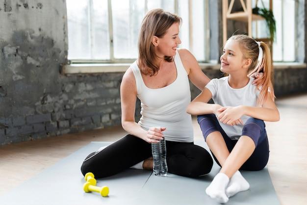 Dochter en moeder op yoga mat kijken naar elkaar