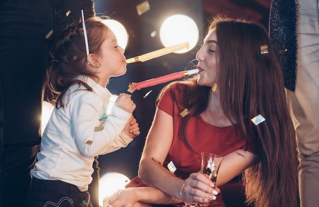 Dochter en moeder plezier tijdens de viering van het nieuwe jaar in het gezelschap van vrienden