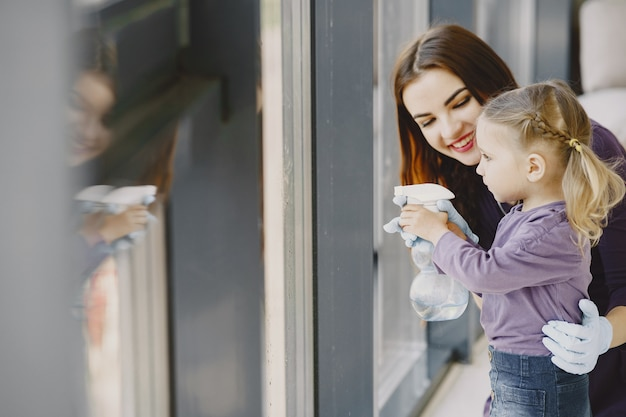 Dochter en moeder schoonmakende venster samen