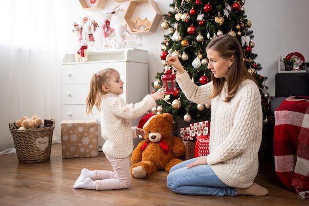 Dochter en moeder spelen thuis in de buurt van de kerstboom