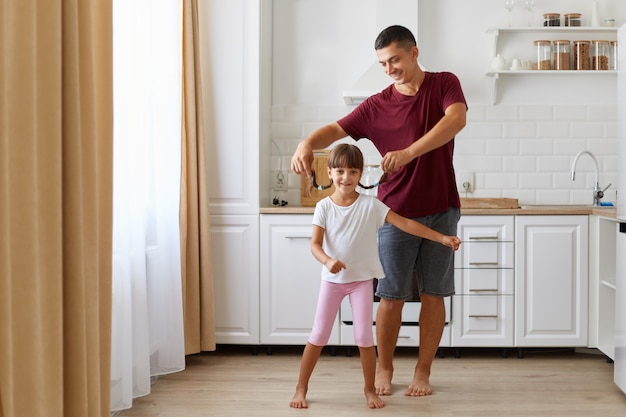 Dochter en vader hebben plezier en dansen in de keuken, mensen die vrijetijdskleding dragen, man die staartjes voor kleine meisjes grootbrengt, gelukkige familie die tijd samen thuis doorbrengt.