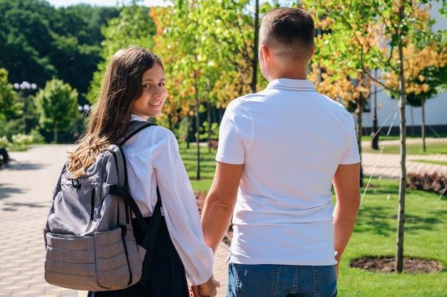 Dochter en vader lopen samen naar school verderop in de straat