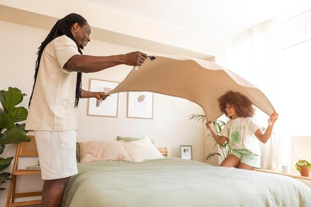 Dochter en vader maken samen het bed op