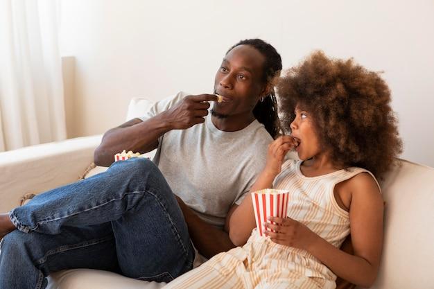 Dochter en vader ontspannen thuis films kijken