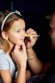 Dochter en vader schilderen een gezicht, hebben plezier