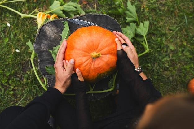 Dochter- en vaderhanden houden een pompoen vast voordat ze aan het snijden zijn voor halloween, bereidt jack o'lantern voor. decoratie voor feest, kleine familie helper, bovenaanzicht, close-up, weergave van bovenaf, kopieer ruimte