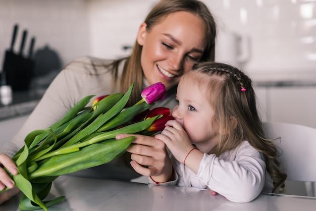 Dochter feliciteert moeder en geeft haar bloemen tulpen
