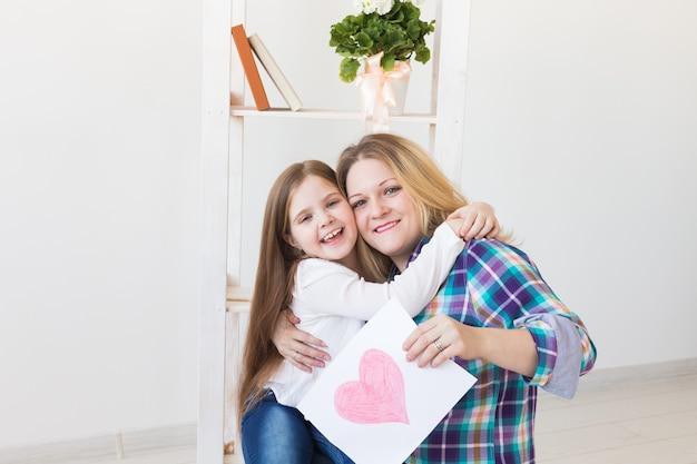 Dochter feliciteert moeder en geeft haar een ansichtkaart
