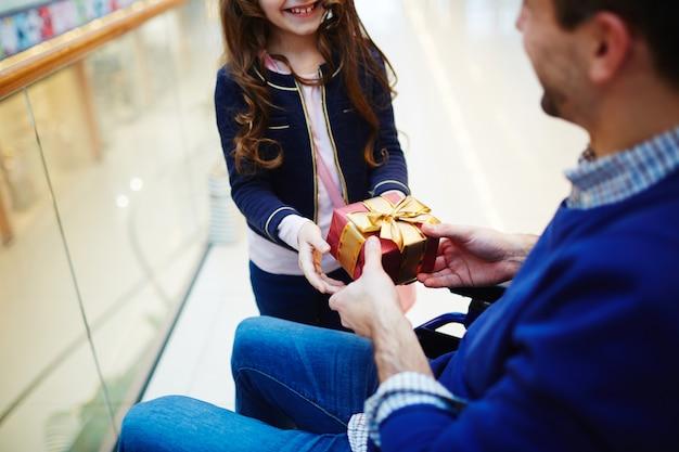 Dochter geeft een cadeau aan haar vader voor vaderdag