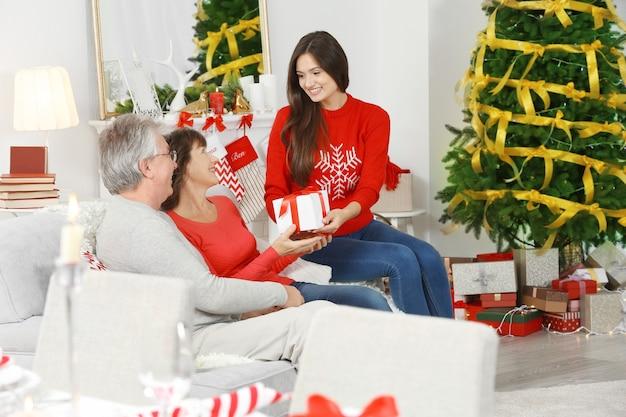 Dochter geeft kerstcadeautjes aan haar bejaarde ouders