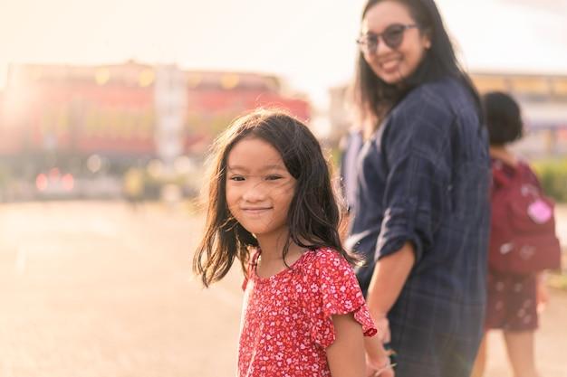 Dochter glimlachen die samen met moeder in zonsondergang of zonsopgangtijd lopen