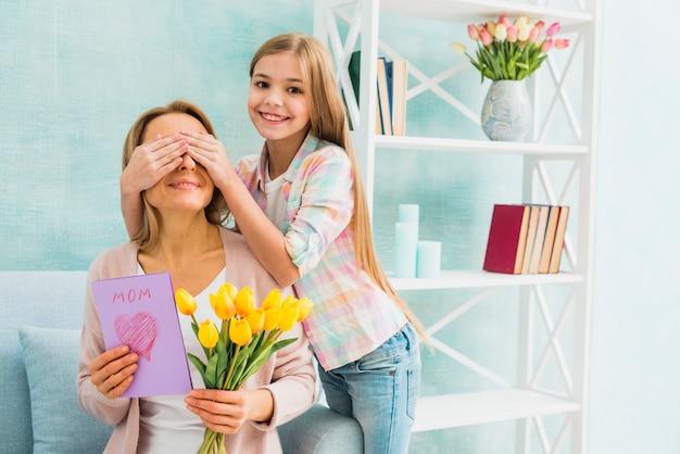 Dochter glimlachend en sluit ogen moeder met geschenken