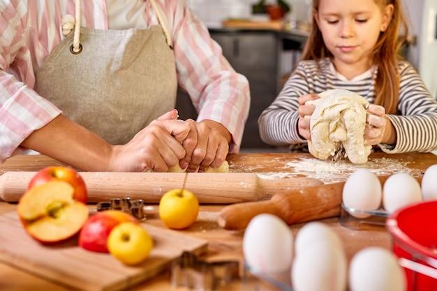Dochter helpen mama kneden voorbereiding deeg in moderne keuken, gelukkig volwassen ouder moeder onderwijs kind helper leren koken bakken taart, geniet van het proces