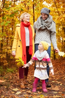 Dochter helpt ouders bladeren verzamelen