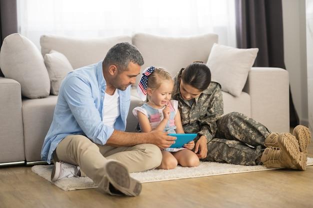 Dochter kijken naar tekenfilm. schattige blonde dochter kijkt naar tekenfilm in de buurt van vader en moeder die in de strijdkrachten dienen