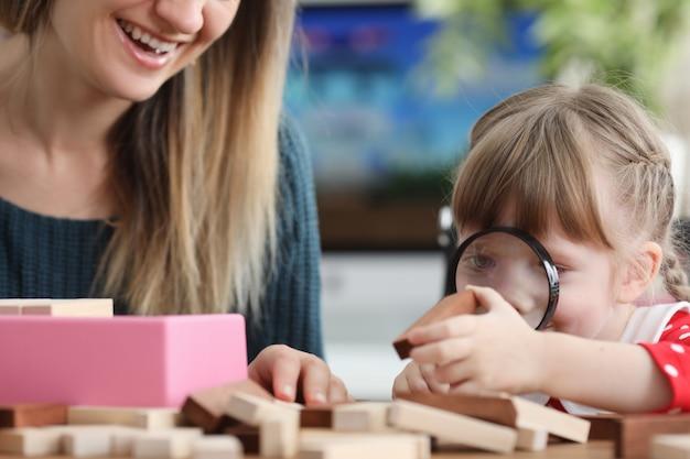 Dochter kijkt door vergrootglas op houten balk