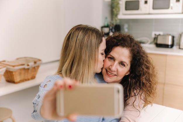 Dochter kussende mamma terwijl het nemen selfie