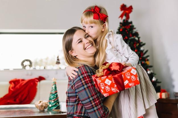 Dochter kussende moeder bij kerstmis