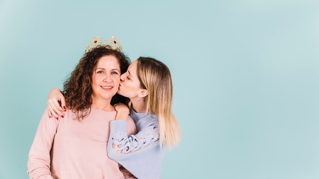 Dochter kussende moeder in kroon
