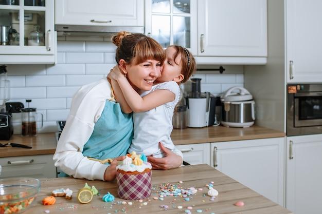Dochter kussende moeder op het moment van het koken van pasen cake