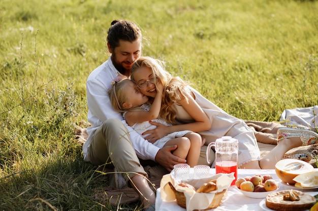 Dochter kust haar moeder. een blije familie. picknick