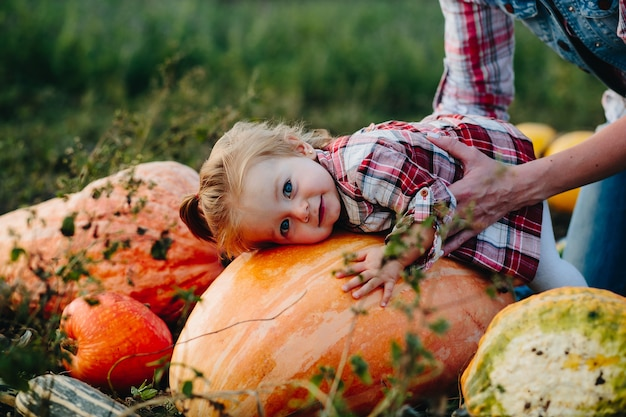 Dochter liggend op een pompoen, en haar moeder staat ernaast