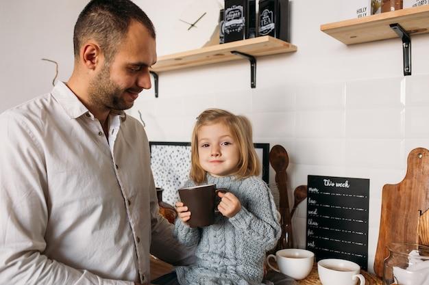 Dochter met haar vader in keuken thuis