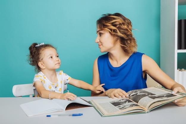 Dochter met moeder samen aan tafel zitten en huiswerk maken.