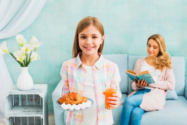 Dochter met ontbijt dat dichtbij moeder glimlacht