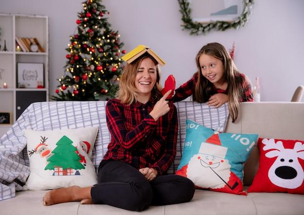 Dochter speelt met kousen die achter haar moeder staan en boek op haar hoofd zitten, zittend op de bank en genieten van kersttijd thuis